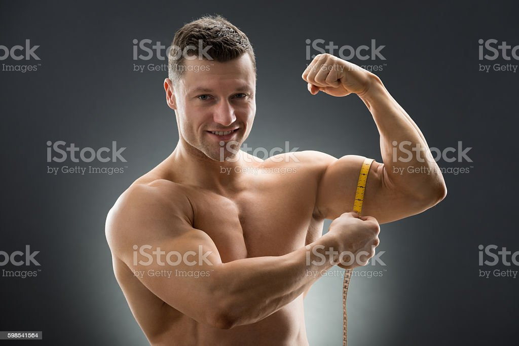 Happy Muscular Man Measuring Bicep With Measure Tape photo libre de droits