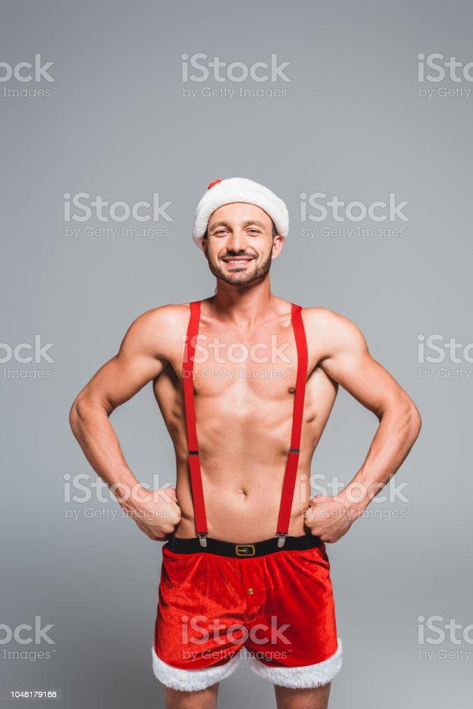 9367e06a3 hombre sin camisa muscular feliz Navidad sombrero y pantalones cortos de  pie con las manos en