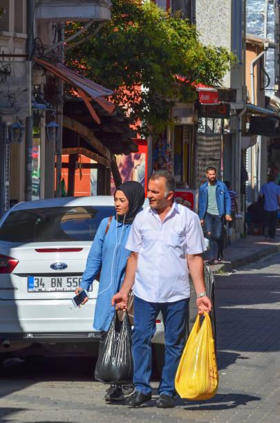 Marketten alışveriş torbaları ile sokakta yürürken mutlu Müslüman aile stok fotoğrafı