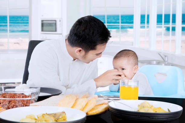glückliche muslimischen vater sein baby füttern - kinderstuhl und tisch stock-fotos und bilder