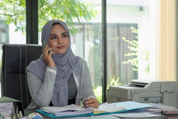 Feliz mujer musulmana llevar hijab con smartphone. - foto de stock