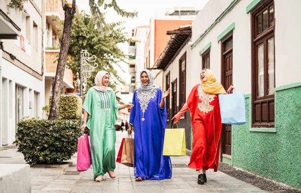 happy muslim women doing shopping in the city center - arabian teen girls having fun buying new traditional arab clothes in mall - concept of people religion, shopper, consumerism and diverse culture - скромная одежда стоковые фото и изображения