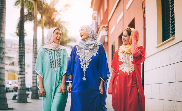 happy muslim women walking in the city center - arabian young girls having fun spending time and laughing together outdoor - concept of people, culture and religion - saudi woman stock photos and pictures