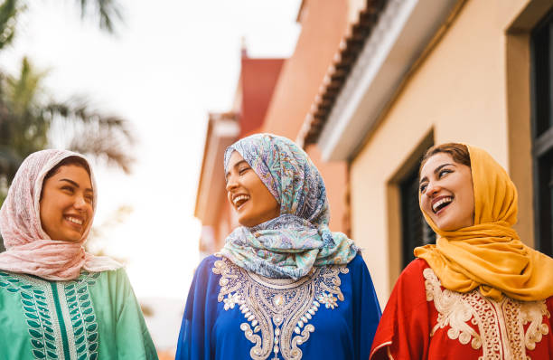 happy muslim women walking in the city center - arabian young girls having fun spending time and laughing together outdoor - concept of people, culture and religion - happy holidays zdjęcia i obrazy z banku zdjęć