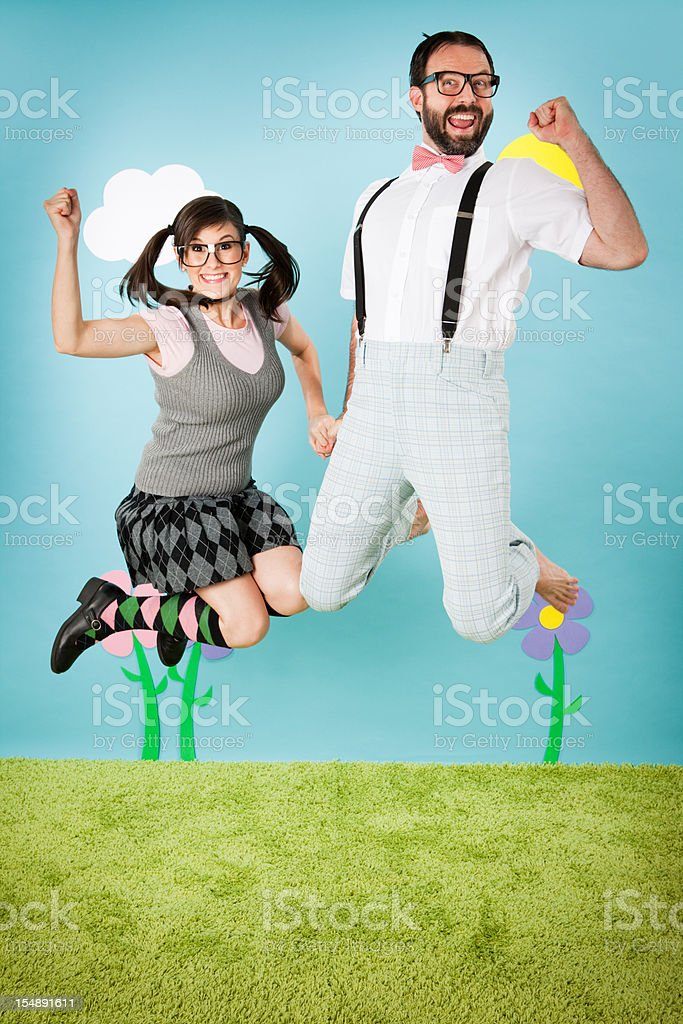 Happy Nerd Couple Holding Hands and Jumping with Excitement royalty-free stock photo