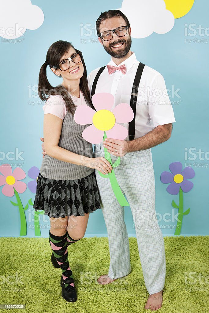 Happy Nerd Couple Hugging and Holding a Flower Outside stock photo