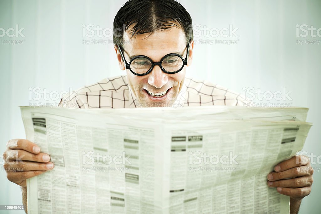 Happy nerd man reading newspaper. royalty-free stock photo