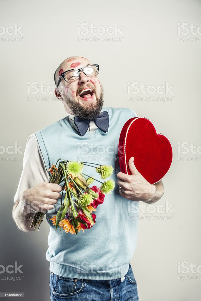 A nerdy man covered in red lipstick kisses holding a colorful bouquet...