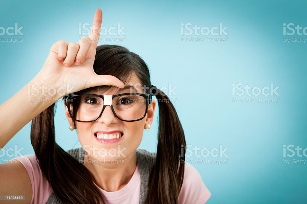 Happy, Nerdy Young Woman Making an 'L' on Her Forehead stock photo