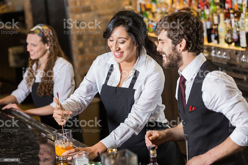 Happy new employee learning to make mixed drinks in bar stock photo