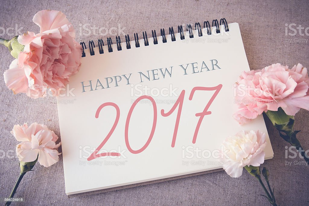 Happy New Year 2017 on Notepad with pink flowers foto royalty-free