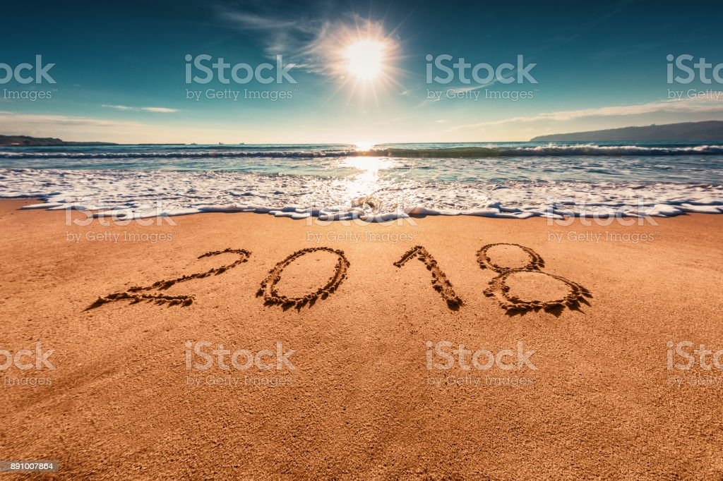 Happy New Year 2018 concept, lettering on the beach. Sea sunrise stock photo