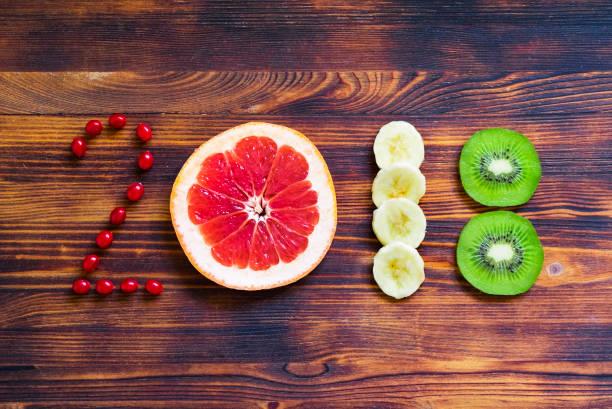 feliz año nuevo 2018 de frutas y bayas en el fondo de madera. - 2018 fotografías e imágenes de stock