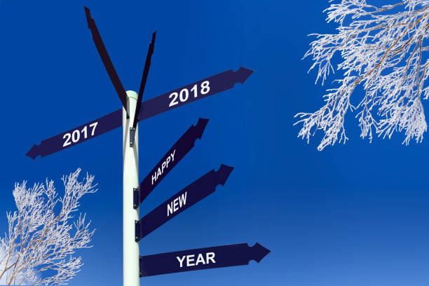 Happy new year 2018 on direction panels, snowy trees stock photo