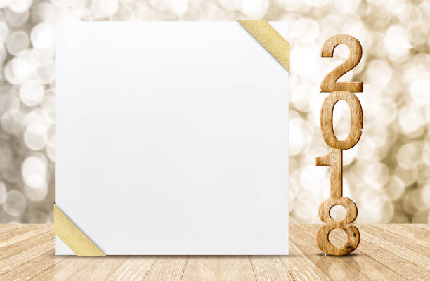 Happy new year 2018 with blank white greeting card with gold ribbon in perspective room at sparkling bokeh wall and wooden plank floor,leave space for display of design stock photo