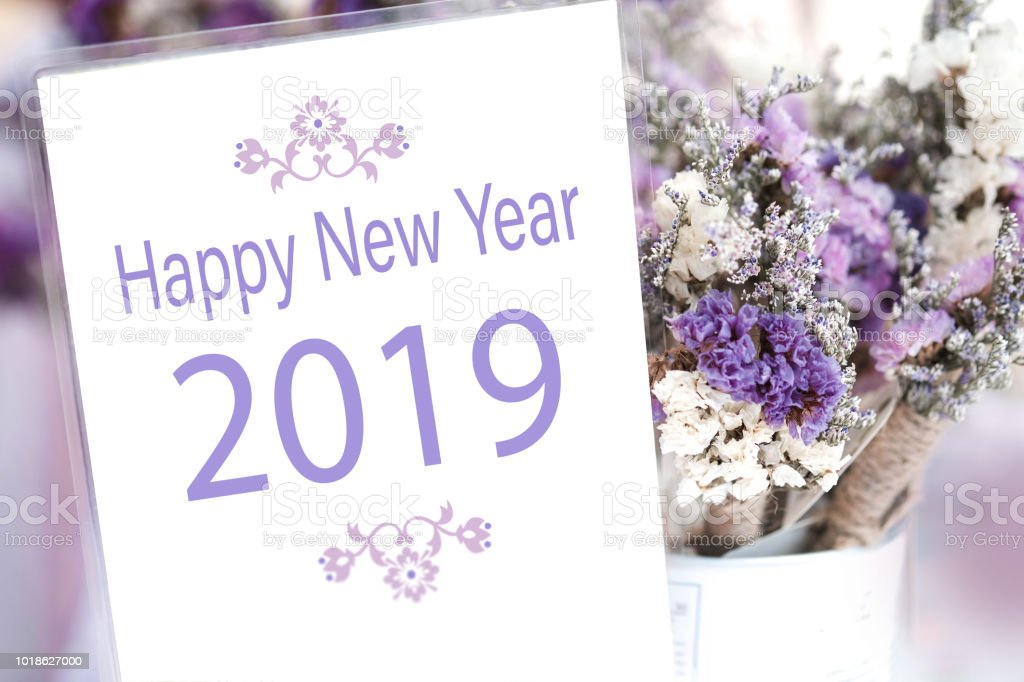 happy new year 2018 word on white card and purple flower background