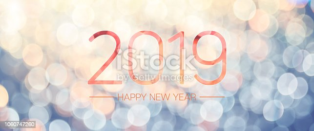 istock Happy new year 2019 banner with pale yellow and blue bokeh light sparkling background,Holiday greeting card. 1060747260