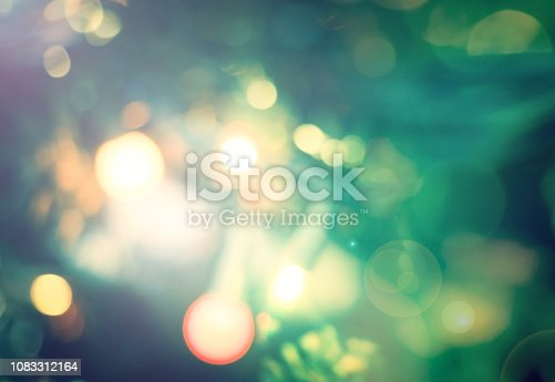 istock Happy new year 2019 concept: Abstract bokeh light bulb and blurred green christmas tree background 1083312164