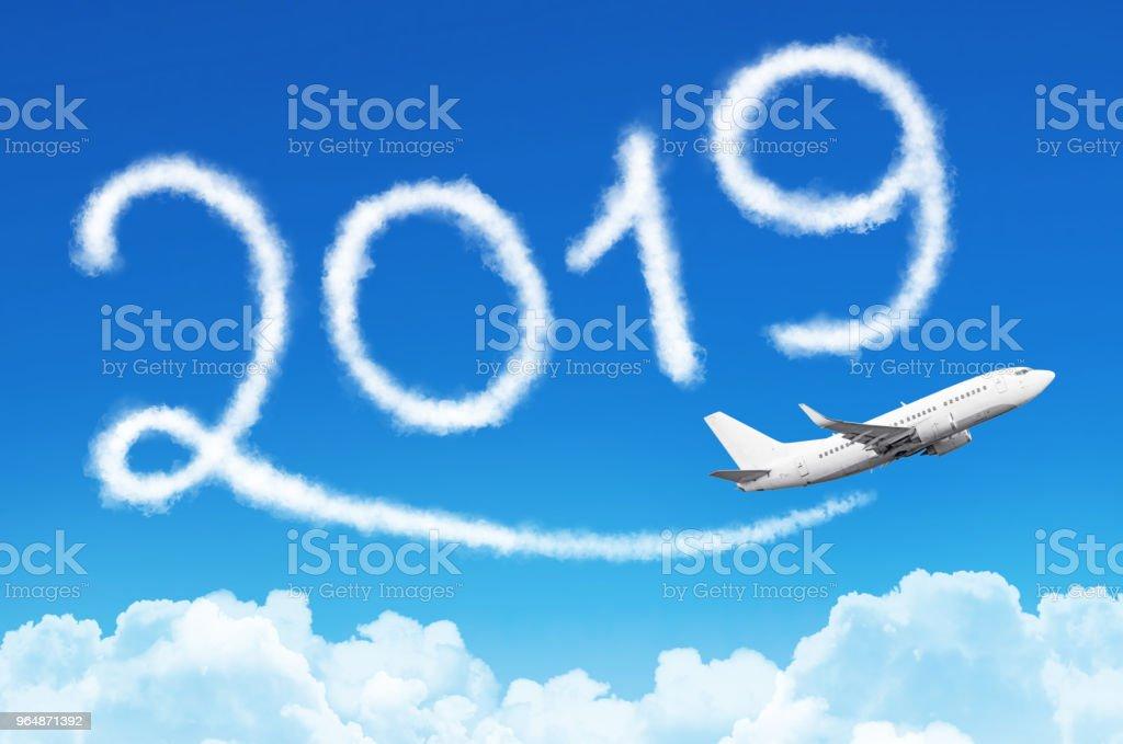 新年快樂2019概念。飛機在天空中的蒸汽軌跡繪製。 - 免版稅2019圖庫照片