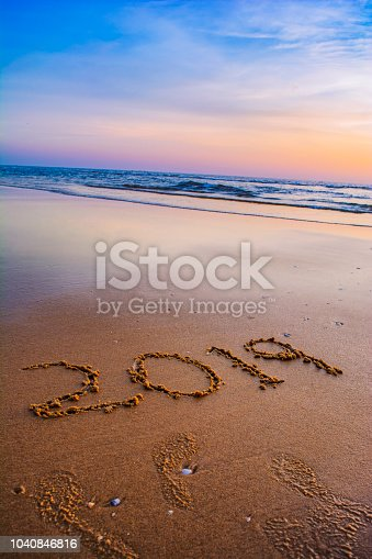 945046208 istock photo Happy New Year 2019 concept, lettering on the beach 1040846816