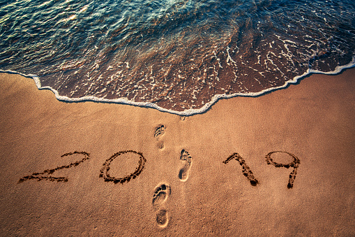 istock Happy New Year 2019 concept written on the beach. Footprints on the sand 1068679820