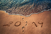 Happy New Year 2019 written on the sand and steps. Beach at sunrise