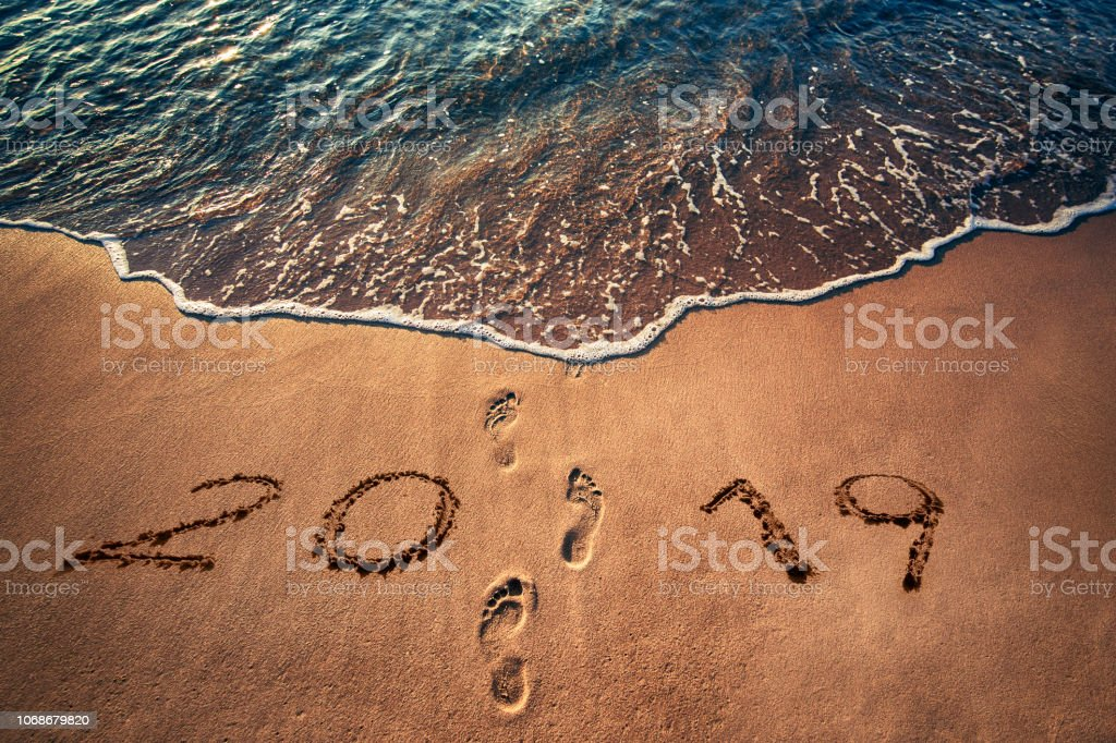 Happy New Year 2019 concept written on the beach. Footprints on the sand stock photo