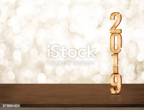 istock Happy New Year 2019 gold glossy with sparkling star on dark brown table with gold bokeh wall,Holiday festive celebration concept.copy space for display of text or content. 973664404