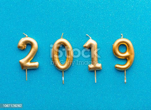 istock Happy new year 2019. Gold shiny number, candles on colored background. Christmas , festive background. 1067126262