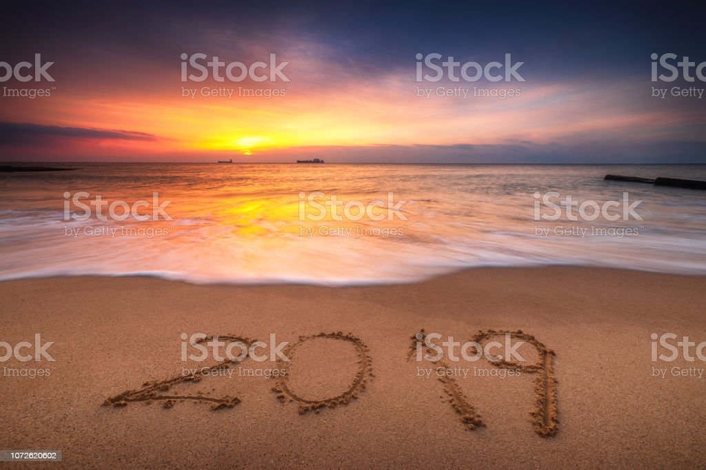 Happy New Year 2019, lettering on the beach. Sea sunrise stock photo