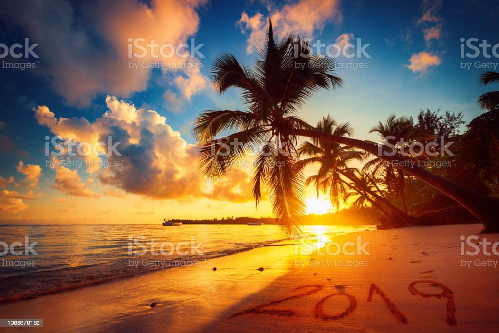 Happy New Year 2019, lettering on  tropical beach. Sea sunrise. Punta Cana stock photo