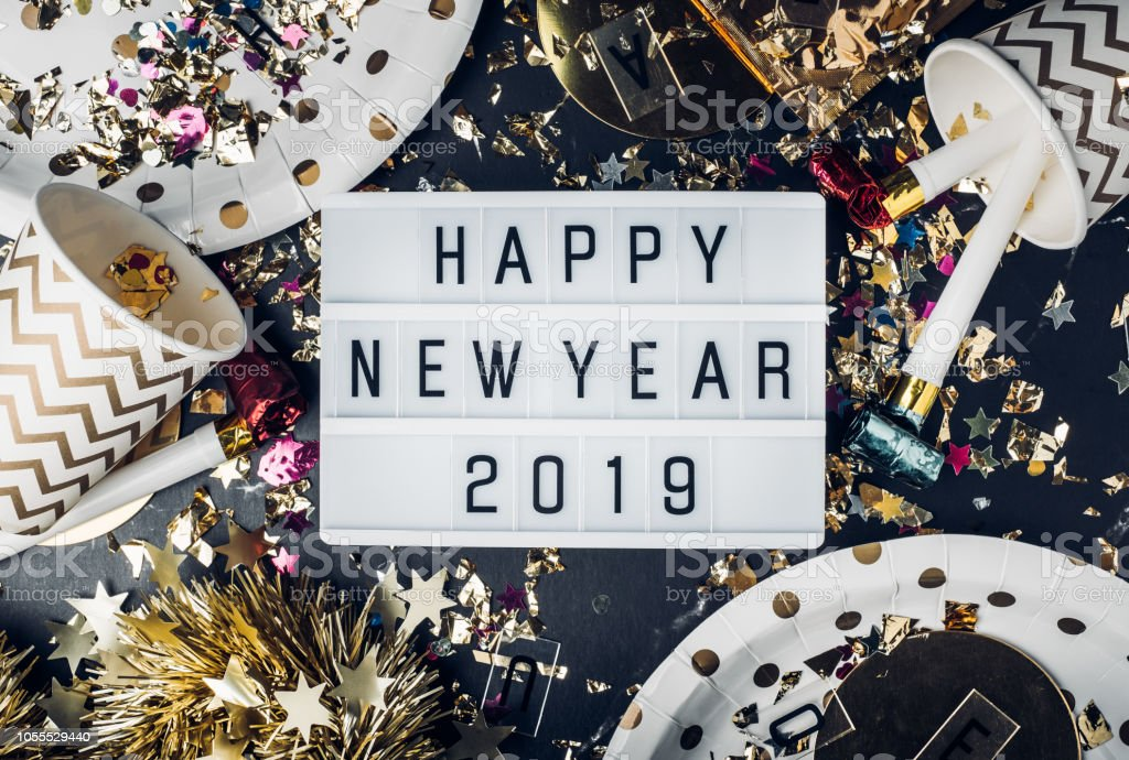 Happy new year 2019 on light box with party cup,party blower,tinsel,confetti.Fun Celebrate holiday party time table top view.