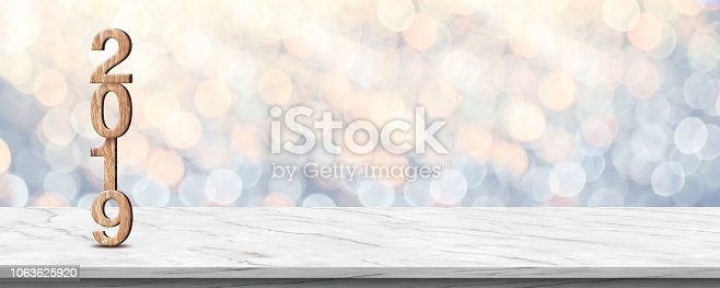 istock Happy new year 2019 (3d rendering wood texture) on white marble table at soft pastel blue and orange sparkle bokeh light abstract background,mock up banner space for holiday greeting card. 1063625920