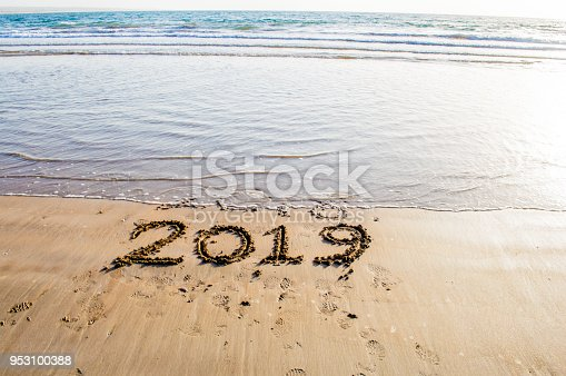 istock Happy New Year 2019 text on the sea beach. Abstract background photo of coming New Year 2019 and leaving year of 2018 953100388