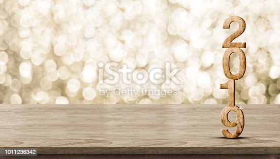 istock Happy New Year 2019 wood with sparkling star on brown wood table with gold bokeh background,Holiday festive celebration concept.Banner mock up for display of product or design content. 1011236342