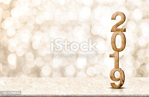 istock Happy New Year 2019 wood with sparkling star on marble table with gold bokeh background,Holiday festive celebration concept.copy space for display of text or content. 1011236534