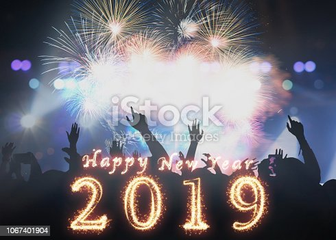 istock Happy new year 2019 written with Sparkle firework on Concert crowd in silhouettes of Music fanclub with show hand action for celebrate with fireworks, Xmas celebration concept 1067401904