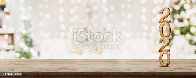 istock happy new year 2020 at woooden table top with abstract warm living room decor with christmas tree string light blur background with snow,Holiday backdrop,Mock up banner for display of product. 1170036694