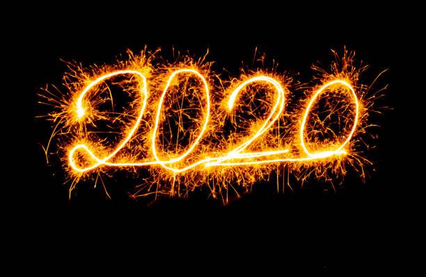 Felizes año nuevo 2020 hermosa brillantes oro números de escrito con chispean fuegos artificiales aislados en el espacio de copia fondo negro en vacaciones de Navidad y año nuevo celebración y diseños de tarjetas de saludos. - foto de stock
