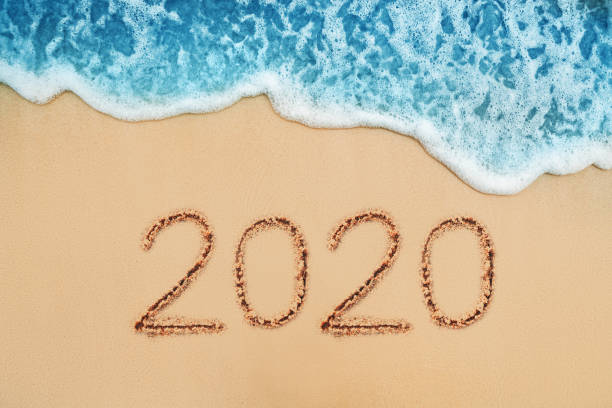 Frohes neues Jahr 2020 Konzept, Schriftzug am Strand. Sonnenaufgang im Meer. – Foto