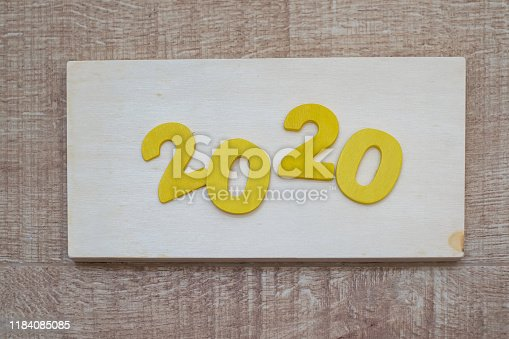 1018565666istockphoto Happy New Year 2020 concept, Wood block 2020 on wooden background 1184085085