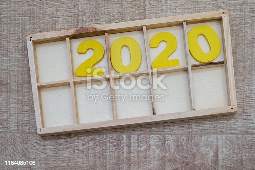 1018565666istockphoto Happy New Year 2020 concept, Wood block 2020 on wooden background 1184085106