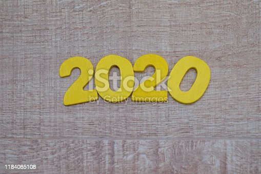1018565666istockphoto Happy New Year 2020 concept, Wood block 2020 on wooden background 1184085108