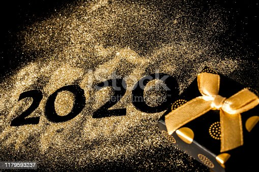 Happy New Year 2020 . Creative Collage of numbers two and zero made up the year 2020. Beautiful sparkling Golden number 2020 and gift on black background for design.