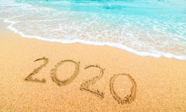 Frohes Neues Jahr 2020, Schriftzug am Strand mit Welle und blauem Meer. Zahlen 2020 Jahr an der Küste, Neujahrskonzept. – Foto