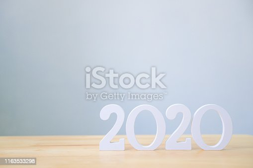 1066508880istockphoto Happy new year 2020, Number wood material on wooden table with white wall background, Copy space 1163533298