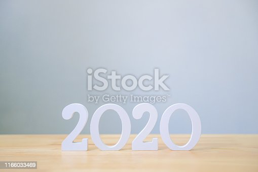 1066508880istockphoto Happy new year 2020, Number wood material on wooden table with white wall background, Copy space 1166033469