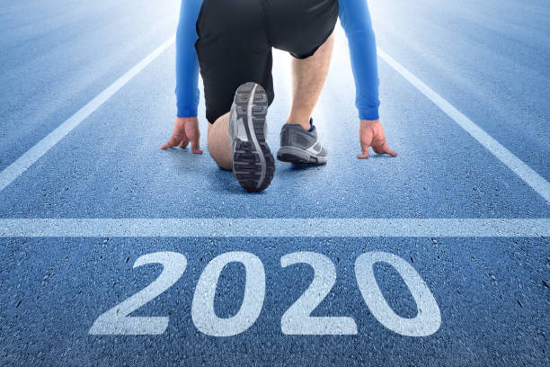 Happy New Year 2020 Runner man ready to run on the 2020 line. Happy New Year 2020 starting line stock pictures, royalty-free photos & images