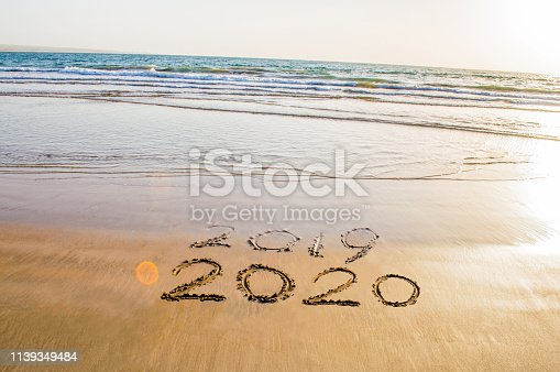 istock Happy New Year 2020 text on the sea beach. Abstract background photo of coming New Year 2020 and leaving year of 2019 1139349484