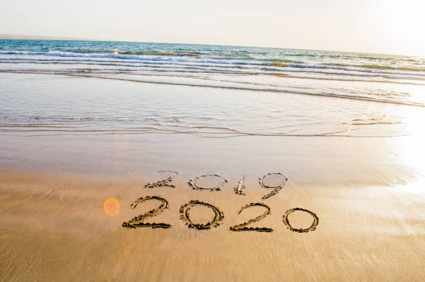 happy new year 2020 text on the sea beach. abstract background photo of coming new year 2020 and leaving year of 2019 - new years day stock pictures, royalty-free photos & images
